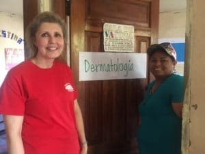 """Photo of Mellissa Binney smiling with a person in front of a door labeled """"dermatologia."""""""